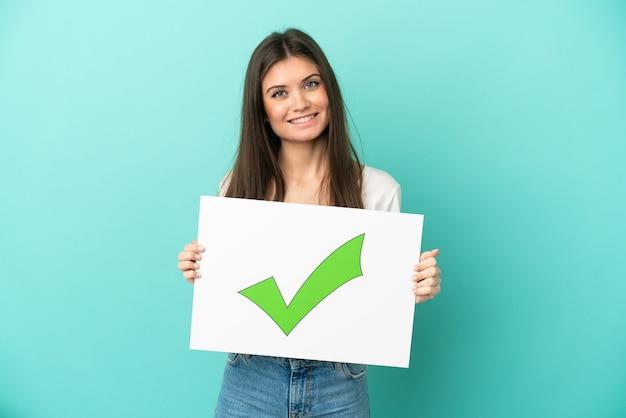 Junge kaukasische frau lokalisiert auf blauem hintergrund, der ein plakat mit grünem häkchensymbol des textes mit glücklichem ausdruck hält