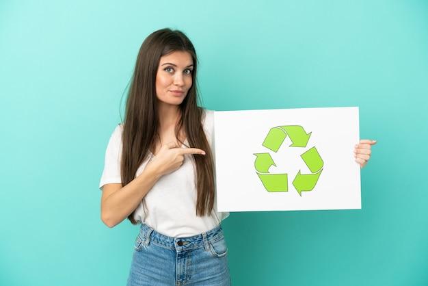 Junge kaukasische frau lokalisiert auf blauem hintergrund, der ein plakat mit recycling-symbol hält und es zeigt
