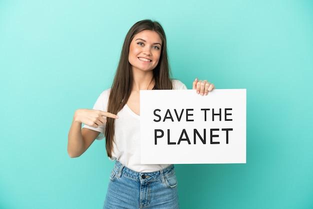 Junge kaukasische frau lokalisiert auf blauem hintergrund, der ein plakat mit text hält speichern sie den planeten und zeigen sie es