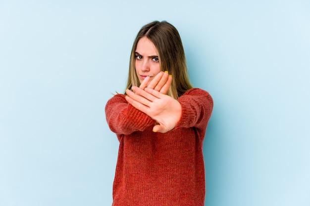 Junge kaukasische frau lokalisiert auf blauem hintergrund stehend mit ausgestreckter hand, die stoppschild zeigt, das sie verhindert.