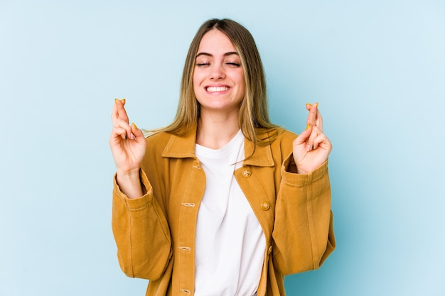 Junge kaukasische frau lokalisiert auf blauen kreuzungsfingern für glück haben