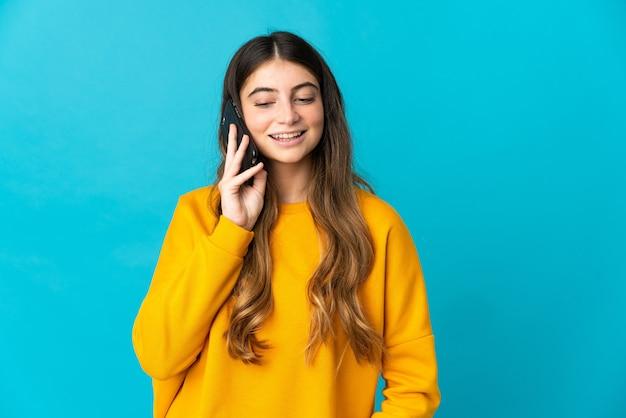 Junge kaukasische frau lokalisiert auf blauer wand, die ein gespräch mit dem mobiltelefon mit jemandem hält