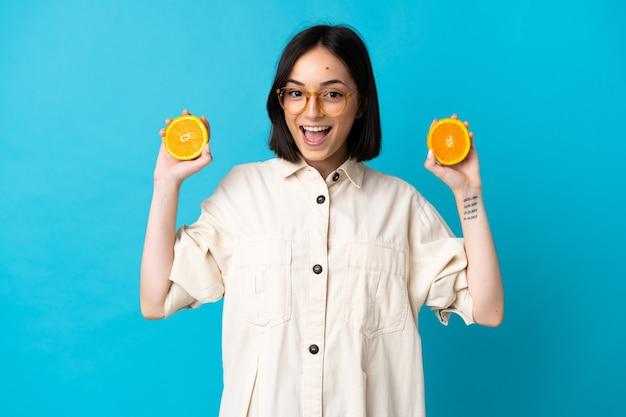 Junge kaukasische frau lokalisiert auf blauer wand, die eine orange hält
