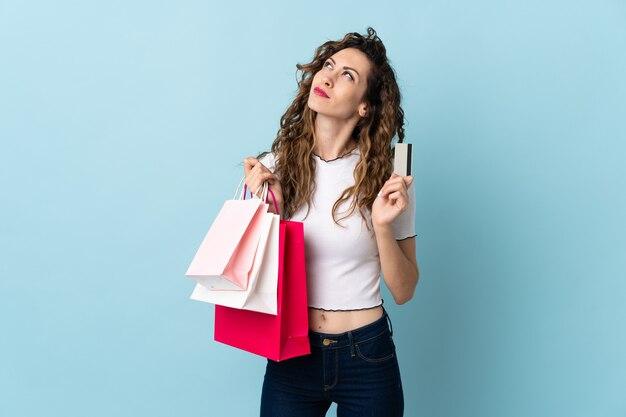 Junge kaukasische frau lokalisiert auf blauer wand, die einkaufstaschen und eine kreditkarte und das denken hält