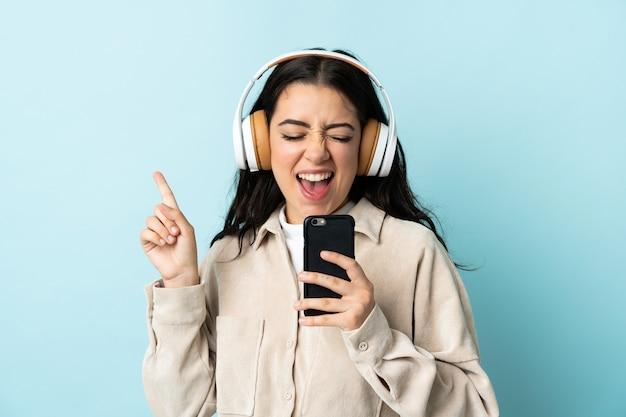 Junge kaukasische frau lokalisiert auf blauer wand, die musik mit einem handy und gesang hört