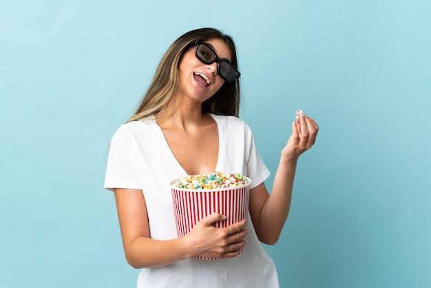 Junge kaukasische frau lokalisiert auf blauer wand mit 3d-brille und hält einen großen eimer popcorn
