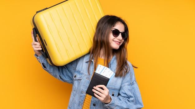 Junge kaukasische frau lokalisiert auf gelb im urlaub mit koffer und pass