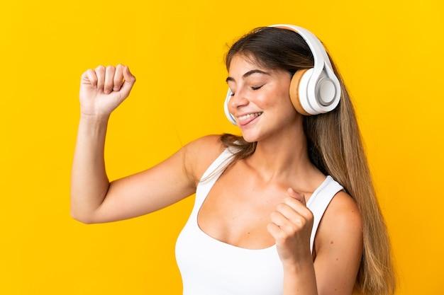 Junge kaukasische frau lokalisiert auf gelbe hörende musik und tanzend