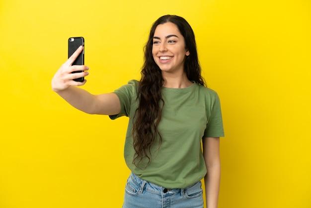 Junge kaukasische frau lokalisiert auf gelbem hintergrund, der ein selfie macht