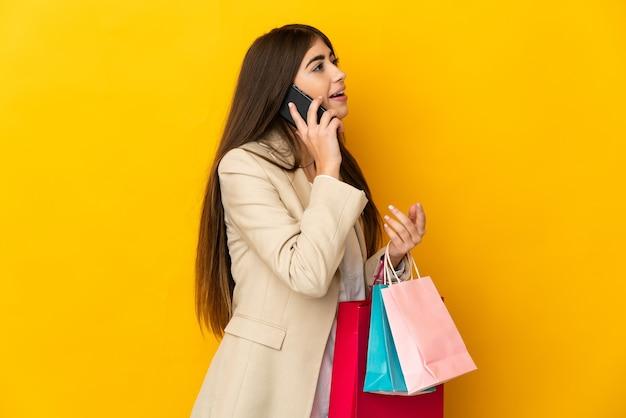 Junge kaukasische frau lokalisiert auf gelbem hintergrund, der einkaufstaschen hält und einen freund mit ihrem handy anruft