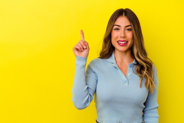 Junge kaukasische frau lokalisiert auf gelbem hintergrund, der nummer eins mit finger zeigt.