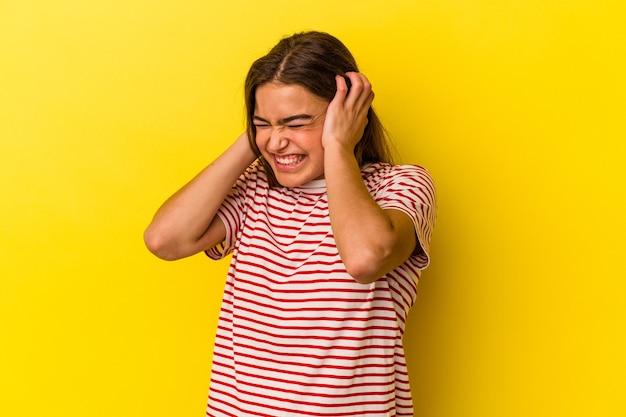 Junge kaukasische frau lokalisiert auf gelbem hintergrund, der ohren mit den händen bedeckt.