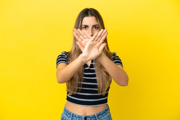 Junge kaukasische frau lokalisiert auf gelbem hintergrund, der stoppgeste mit ihrer hand macht, um eine handlung zu stoppen