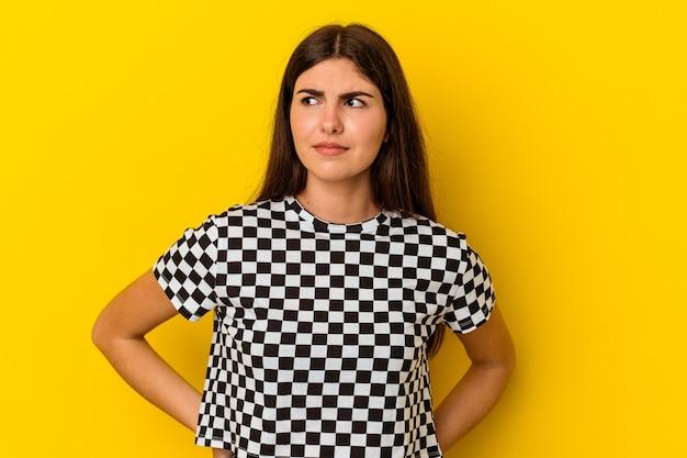 Junge kaukasische frau lokalisiert auf gelbem hintergrund verwirrt, fühlt sich zweifelhaft und unsicher.