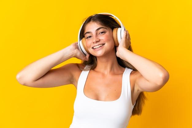 Junge kaukasische frau lokalisiert auf gelber hörender musik