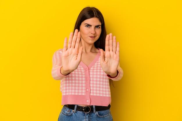 Junge kaukasische frau lokalisiert auf gelber wand, die mit ausgestreckter hand steht, die stoppschild zeigt, das sie verhindert