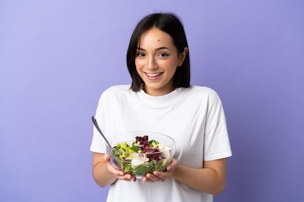 Junge kaukasische frau lokalisiert auf lila, die eine schüssel salat mit glücklichem ausdruck hält