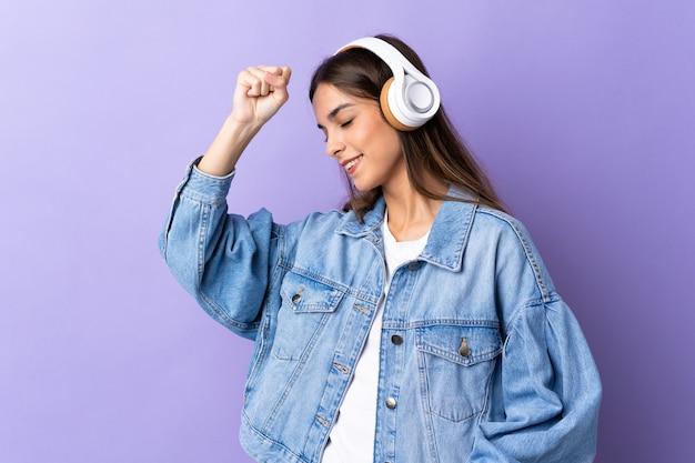 Junge kaukasische frau lokalisiert auf lila hörende musik und tanzend