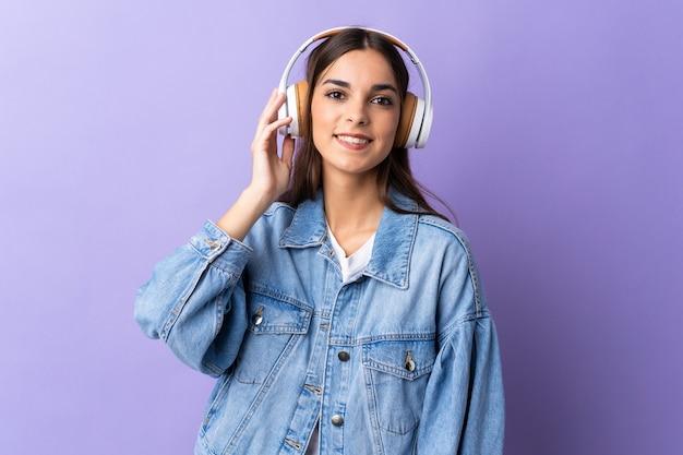 Junge kaukasische frau lokalisiert auf lila hörende musik