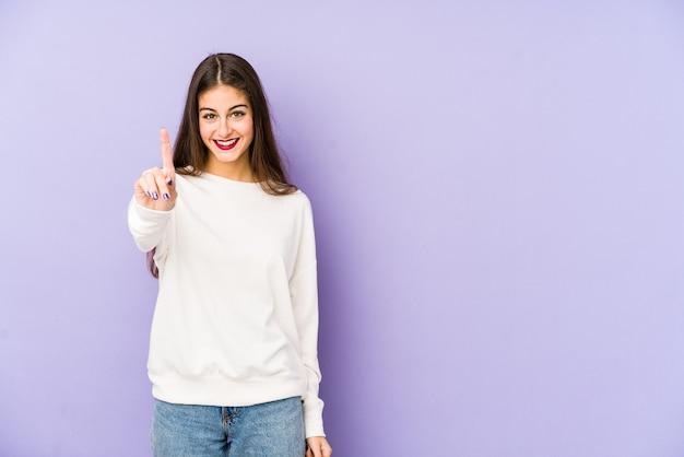 Junge kaukasische frau lokalisiert auf purpur, das nummer eins mit finger zeigt.