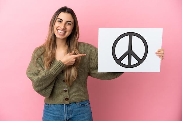Junge kaukasische frau lokalisiert auf rosa hintergrund, der ein plakat mit friedenssymbol hält und es zeigt