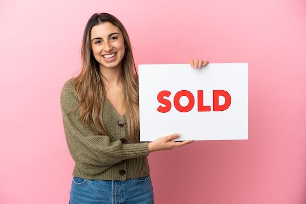 Junge kaukasische frau lokalisiert auf rosa hintergrund, der ein plakat mit text verkauft mit glücklichem ausdruck hält