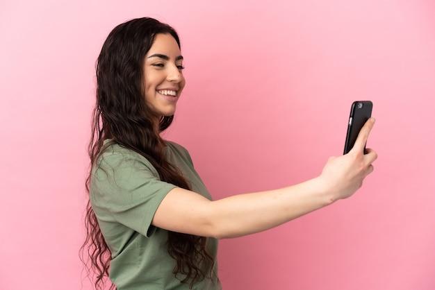 Junge kaukasische frau lokalisiert auf rosa hintergrund, der ein selfie mit handy macht