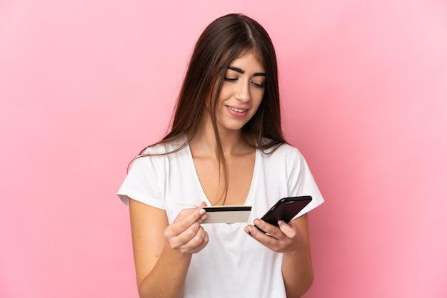 Junge kaukasische frau lokalisiert auf rosa hintergrund, der mit dem handy mit einer kreditkarte kauft