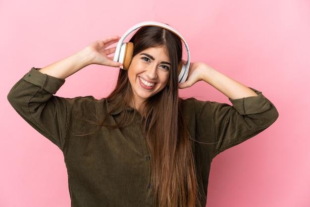 Junge kaukasische frau lokalisiert auf rosa hintergrund, der musik hört