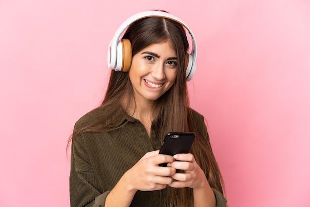 Junge kaukasische frau lokalisiert auf rosa hintergrund, der musik mit einem handy hört und vorne schaut