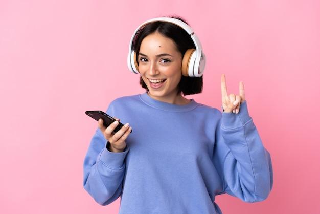 Junge kaukasische frau lokalisiert auf rosa hörende musik mit einem handy, das rockgeste macht