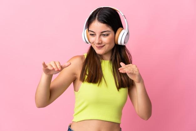 Junge kaukasische frau lokalisiert auf rosa hörende musik und tanzend