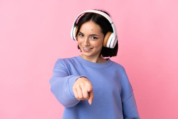 Junge kaukasische frau lokalisiert auf rosa hörende musik