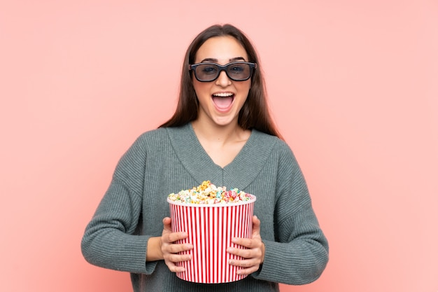 Junge kaukasische frau lokalisiert auf rosa mit 3d brille und hält einen großen eimer popcorn