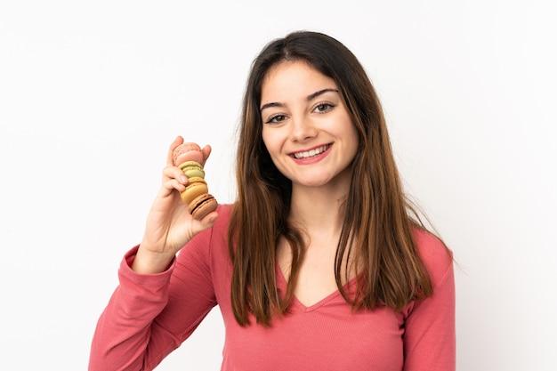Junge kaukasische frau lokalisiert auf rosa wand, die bunte französische macarons hält und viel lächelt