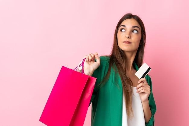 Junge kaukasische frau lokalisiert auf rosa wand, die einkaufstaschen und eine kreditkarte und das denken hält