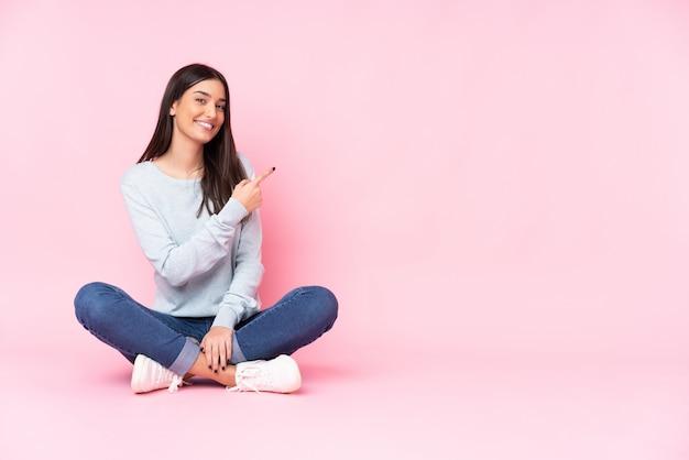 Junge kaukasische frau lokalisiert auf rosa wand, die finger zur seite zeigt