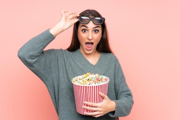 Junge kaukasische frau lokalisiert auf rosa wand überrascht mit 3d-brille und hält einen großen eimer popcorn