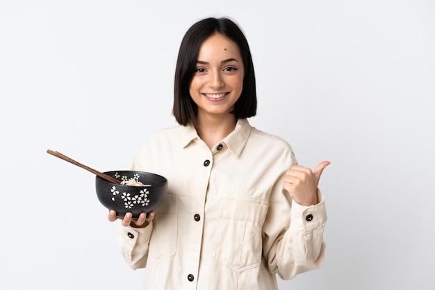 Junge kaukasische frau lokalisiert auf weiß, das zur seite zeigt, um ein produkt zu präsentieren, während eine schüssel nudeln mit stäbchen hält