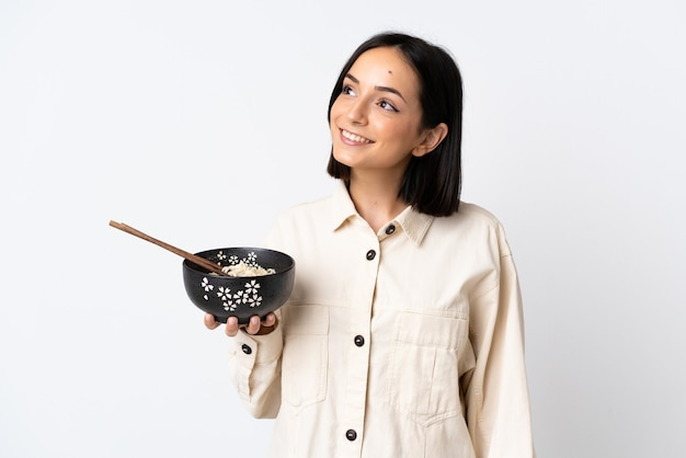 Junge kaukasische frau lokalisiert auf weißem aufschauen beim lächeln beim halten einer schüssel nudeln mit essstäbchen