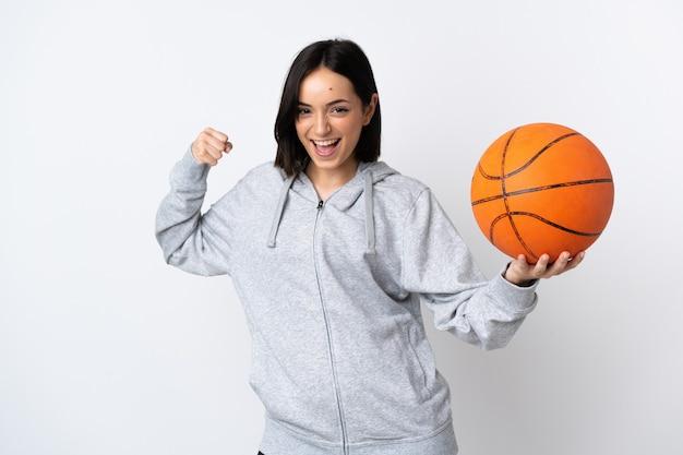 Junge kaukasische frau lokalisiert auf weißem hintergrund, der basketball spielt