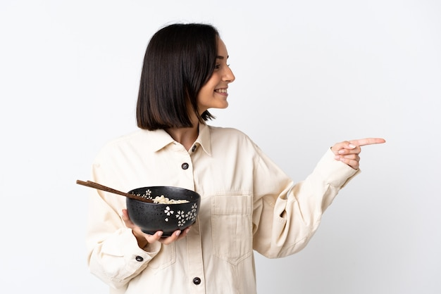 Junge kaukasische frau lokalisiert auf weißer wand, die zur seite zeigt, um ein produkt zu präsentieren, während eine schüssel nudeln mit essstäbchen hält