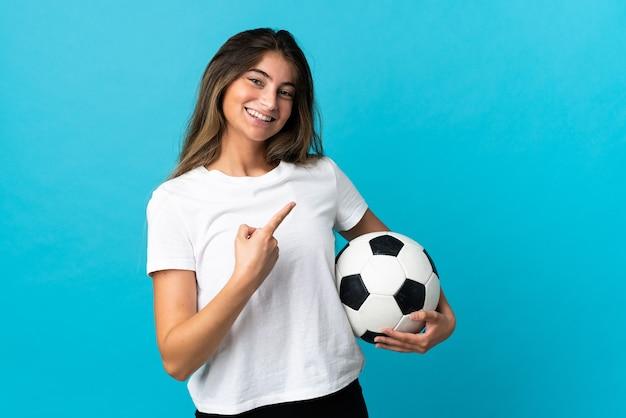 Junge kaukasische frau lokalisiert mit fußball und zeigt auf die seite