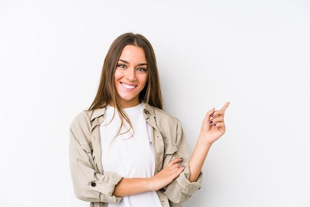 Junge kaukasische frau lokalisiertes lächeln, das freundlich mit dem zeigefinger weg zeigt.