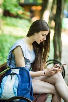 Junge kaukasische frau mit einem handy, sitzend in einem park auf einer holzbank, eine sms lesend.