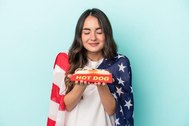Junge kaukasische frau mit einem hot dog auf blauem hintergrund isoliert