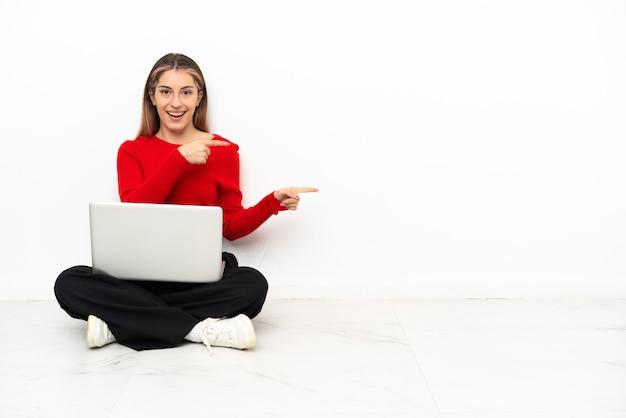 Junge kaukasische frau mit einem laptop, der auf dem boden sitzt, überrascht und seite zeigend