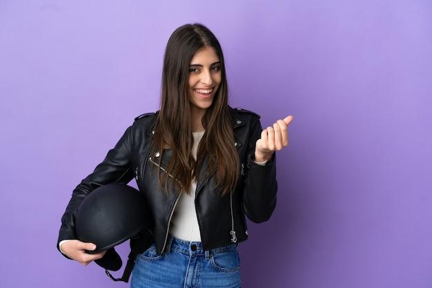 Junge kaukasische frau mit einem motorradhelm auf violettem hintergrund isoliert, die geldgeste macht