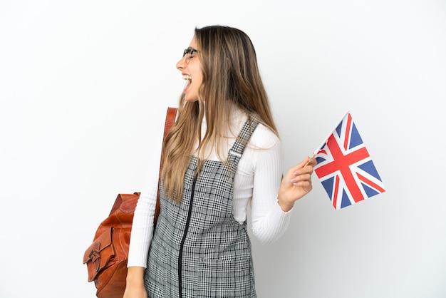 Junge kaukasische frau mit einer flagge des vereinigten königreichs isoliert auf weißem hintergrund lachend in seitenlage
