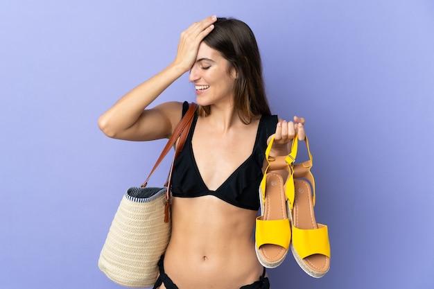 Junge kaukasische frau mit einer strandtasche, die sandalen auf violettem hintergrund hält, hat etwas erkannt und beabsichtigt die lösung